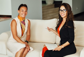 Two women talking on a couch